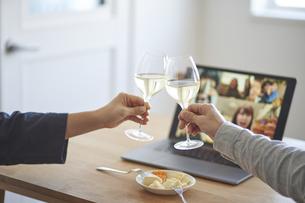 男女が乾杯をする手とリモート飲みをするパソコンの画面の写真素材 [FYI04782797]