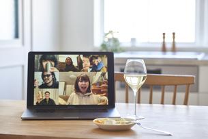 リモート飲みをしているパソコンの画面と白ワインとおつまみの写真素材 [FYI04782800]