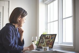 キッチンでリモート飲みをする女性の写真素材 [FYI04782804]