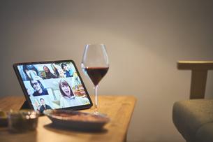 リモート飲みをしているパソコンの画面と赤ワインとおつまみの写真素材 [FYI04782827]