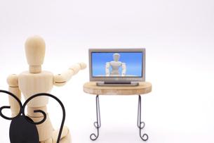 テレビ画面に向かって手を出して指摘するデッサン人形の写真素材 [FYI04783280]