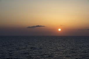 水平線に沈む夕陽の写真素材 [FYI04783485]
