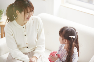 ソファに座り遊ぶ母親と娘の写真素材 [FYI04784264]