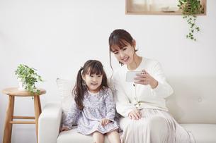 ソファに座りスマホを見る母親と娘の写真素材 [FYI04784268]