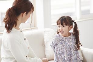 ソファに座り遊ぶ母親と娘の写真素材 [FYI04784270]