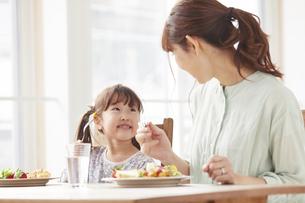 ダイニングテーブルで食事をする母親と娘の写真素材 [FYI04784274]