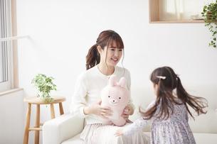 ソファに座り遊ぶ母親と娘の写真素材 [FYI04784278]