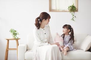 ソファに座り遊ぶ母親と娘の写真素材 [FYI04784284]