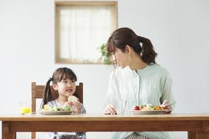ダイニングテーブルで食事をする母親と娘の写真素材 [FYI04784288]