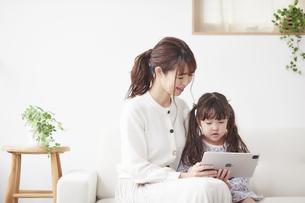 ソファに座りタブレットPCを操作する母親と娘の写真素材 [FYI04784290]