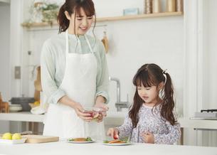 キッチンに立ち料理を作る母親と手伝う女の子の写真素材 [FYI04784291]