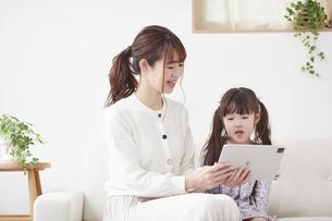 ソファに座りタブレットPCを操作する母親と娘の写真素材 [FYI04784296]
