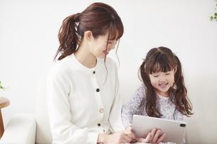 ソファに座りタブレットPCを操作する母親と娘の写真素材 [FYI04784310]