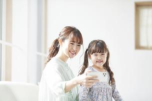 ソファに座りスマホを持つ母親と娘の写真素材 [FYI04784316]