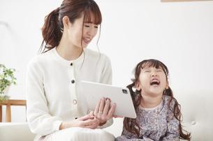 ソファに座りタブレットPCを操作する母親と娘の写真素材 [FYI04784319]