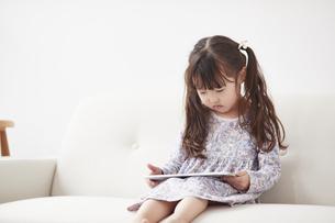 ソファに座りタブレットPCを操作する女の子の写真素材 [FYI04784328]