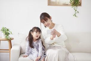 ソファに座りスマホを持つ母親と娘の写真素材 [FYI04784334]