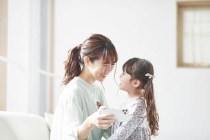 ソファに座りスマホを持つ母親と娘の写真素材 [FYI04784341]
