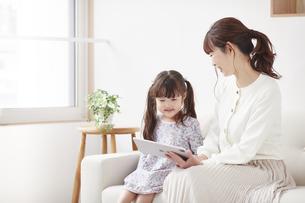 ソファに座りタブレットPCを操作する女の子の写真素材 [FYI04784347]