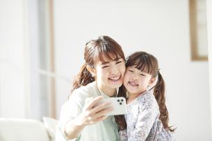 ソファに座りスマホを持つ母親と娘の写真素材 [FYI04784349]