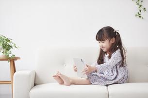 ソファに座りタブレットPCを操作する女の子の写真素材 [FYI04784351]