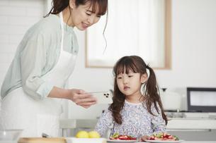 キッチンでスマホを見る母親と娘の写真素材 [FYI04784359]
