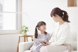 ソファに座りタブレットPCを操作する母親と娘の写真素材 [FYI04784364]