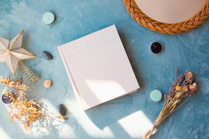 青い背景に置かれた白い生成りのアルバムブックの表紙の写真素材 [FYI04784566]