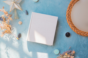 青い背景に置かれた白い生成りのアルバムブックの表紙の写真素材 [FYI04784567]