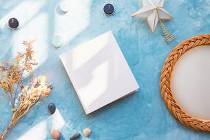 青い背景に置かれた白い生成りのアルバムブックの表紙の写真素材 [FYI04784568]