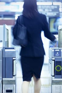 改札機を通るビジネスウーマンの後姿の写真素材 [FYI04784882]