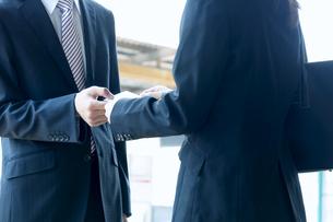 名刺交換するビジネスマンとビジネスウーマンの写真素材 [FYI04784910]