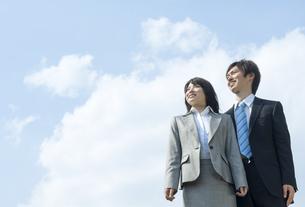 青空の下で遠くを見つめる男性と女性の写真素材 [FYI04784922]