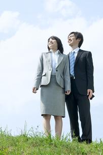 青空の下で遠くを見つめる男性と女性の写真素材 [FYI04784924]