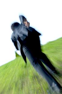 芝生を走るビジネスマンの写真素材 [FYI04784927]