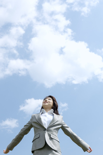 青空の下で遠くを見つめるビジネスウーマンの写真素材 [FYI04784928]