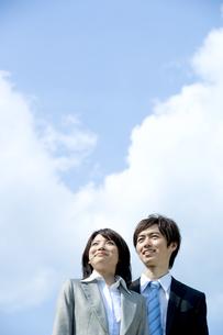 青空の下で遠くを見つめる男性と女性の写真素材 [FYI04784935]