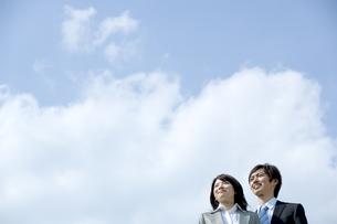 青空の下で遠くを見つめる男性と女性の写真素材 [FYI04784936]