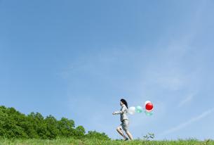 風船を持って走るビジネスウーマンの写真素材 [FYI04784941]