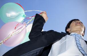 風船を持って走るビジネスマンの写真素材 [FYI04784953]