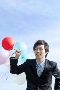 風船を持って走るビジネスマンの写真素材 [FYI04784955]