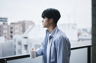 ベランダでコーヒーを飲む男性の写真素材 [FYI04785305]