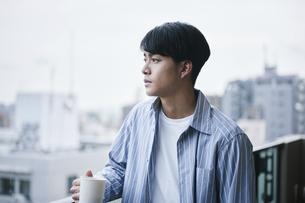ベランダでコーヒーを飲む男性の写真素材 [FYI04785308]