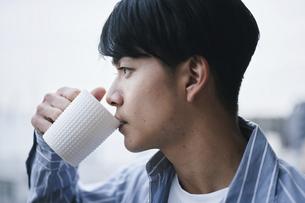 ベランダでコーヒーを飲む男性の写真素材 [FYI04785310]