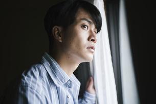 カーテンを開けて外を眺める男性の写真素材 [FYI04785321]