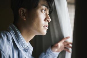 カーテンを開けて外を眺める男性の写真素材 [FYI04785325]