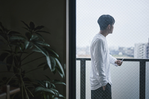 ベランダでタバコを吸う男性の写真素材 [FYI04785329]