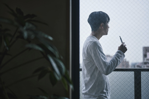 ベランダでタバコを吸う男性の写真素材 [FYI04785332]