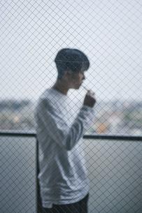 ベランダでタバコを吸う男性の写真素材 [FYI04785333]