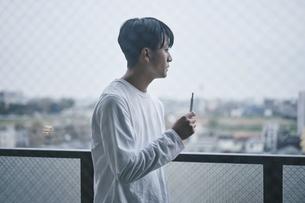 ベランダでタバコを吸う男性の写真素材 [FYI04785334]